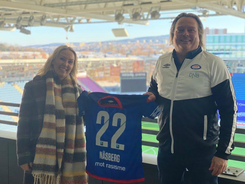 Christina Bøttger og salgssjef Glenn Jensen viser stolt frem drakta med nummer 22 på ryggen. Dette som et symbol på den nye avtalen ut 2022 (Foto: VIF Media)